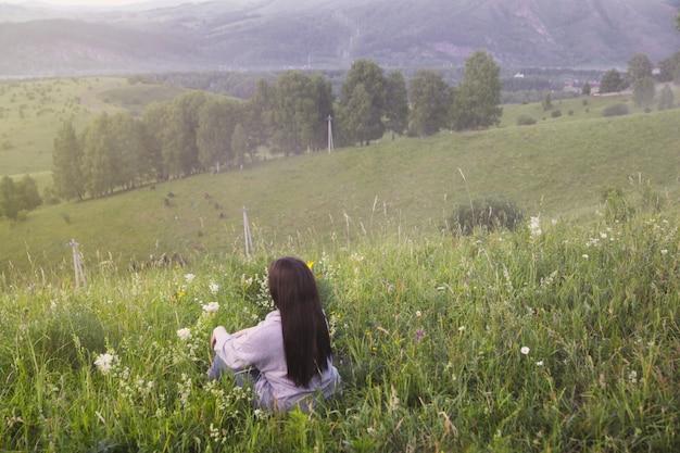 La ragazza sta con la schiena sullo sfondo delle montagne