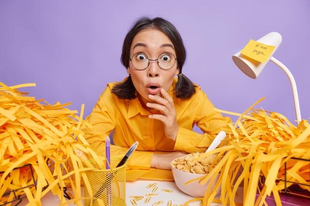 La ragazza fissa gli occhi infastiditi posa sul desktop disordinato circondata da pile di carta ha molti compiti da finire sul viola