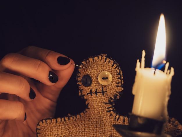 Una ragazza attacca i perni in una bambola voodoo fatta di tela da imballaggio, primo piano. la bambola voodoo alla misteriosa luce di una candela.