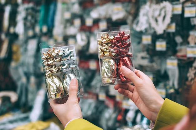 La ragazza del negozio tiene tra le mani gli ornamenti decorativi di capodanno per l'albero.