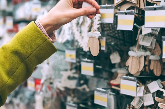 La ragazza del negozio tiene in mano i guanti per le decorazioni decorative di capodanno.