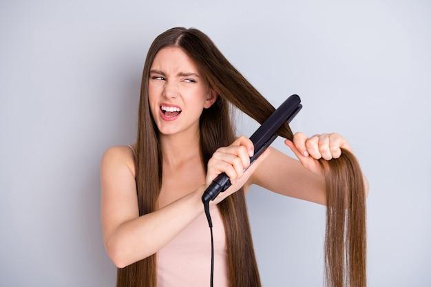Ragazza che raddrizza i capelli con piastra per capelli