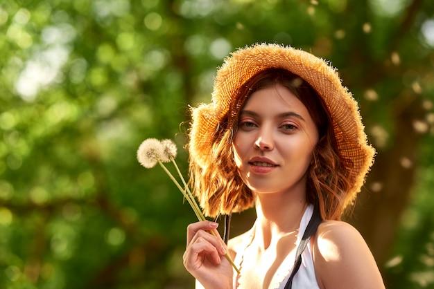 Ragazza in un cappello di paglia con denti di leone in sole estivo mani