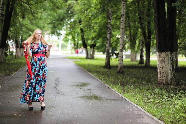 Ragazza in strada con un ombrello per una passeggiata in un giorno d'estate