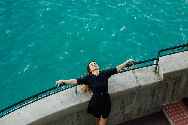 La ragazza allunga le braccia attorno alla scogliera. vista mare relax, liberazione.