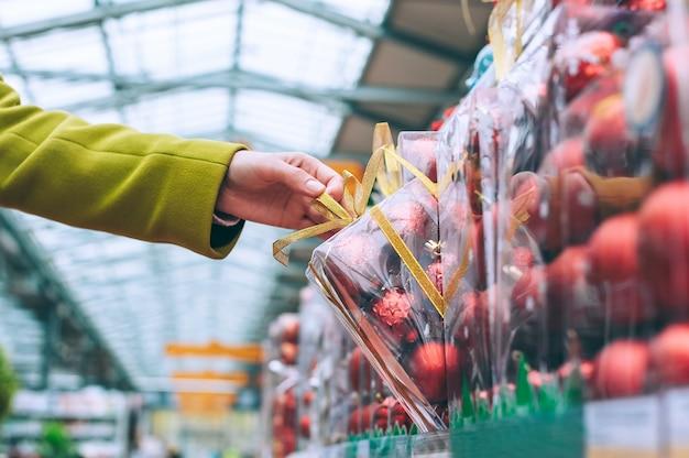 La ragazza allunga la mano dal bancone del negozio, palle decorative decorative per natale e capodanno.