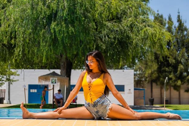 Ragazza che si estende a bordo piscina, allargò le gambe