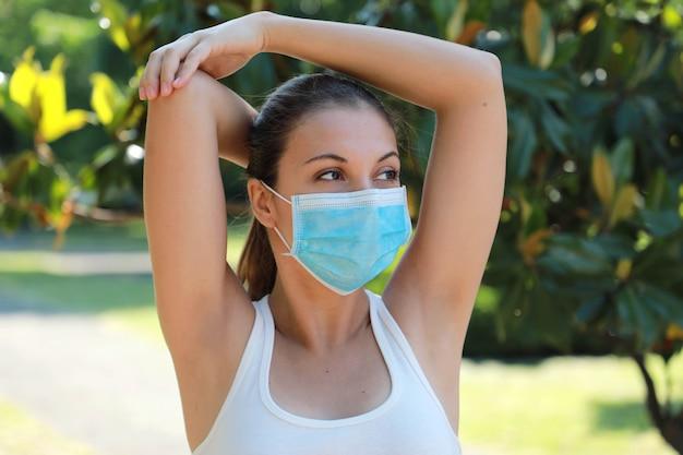 Ragazza che allunga nel parco che mostra le ascelle rasate glabre. donna con mascherina chirurgica.