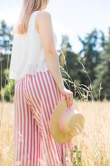 Ragazza in culotte a righe con un cappello di paglia in mano, vista di spalle