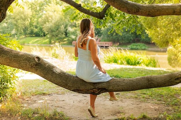Vestito a righe da ragazza seduta da sola su un albero e guardando il lago