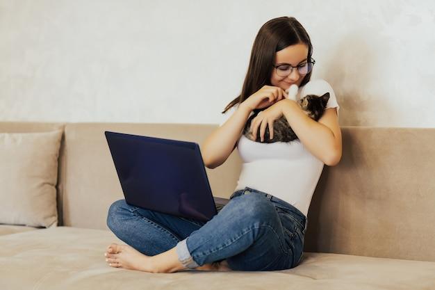 Studentessa freelance lavora a casa su un compito e gioca con il suo piccolo simpatico gatto