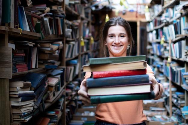 Una studentessa tiene una pila di libri in biblioteca, cerca la letteratura e si offre di leggere, una donna si prepara allo studio, la conoscenza è potere, il libraio di concetto