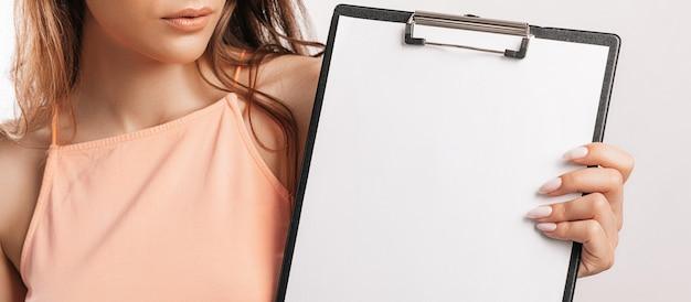 La studentessa indica il foglio. la bella giovane donna di affari tiene una lavagna per appunti con lo spazio in bianco del modello isolato su fondo grigio. studio e concetto di business. copertura didattica online