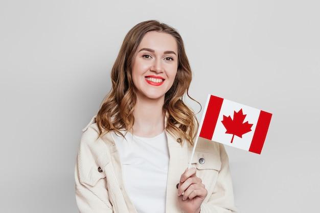 Studentessa che sorride e che tiene una piccola bandiera del canada e che distoglie lo sguardo isolata sopra fondo grigio