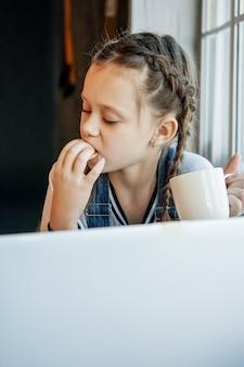 La studentessa studia online con l'insegnante di videochiamata, la ragazza felice ascolta la lezione guarda al computer portatile a casa e beve il tè e? mangiare i biscotti. covid-19-coronavirus.