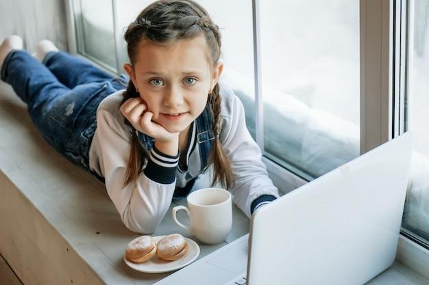Una studentessa studia online con un insegnante di videochiamata al computer portatile a casa e beve tè e mangia biscotti