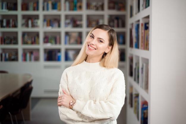 Studentessa nella biblioteca universitaria, sullo sfondo gli scaffali con i libri.