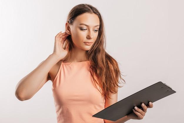 La studentessa scrive le informazioni. bella giovane donna d'affari isolata su sfondo grigio. raggiungere il concetto di affari di ricchezza di carriera. spazio della copia del modello. tieni un blocco per appunti con i documenti