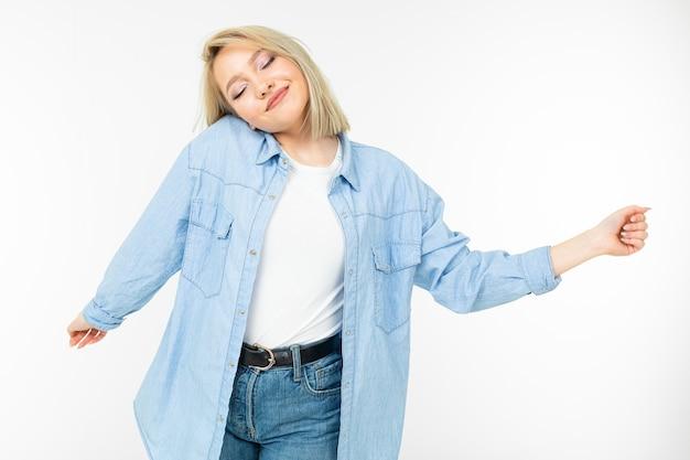 Ragazza in un'immagine elegante agitando i capelli e ballando su uno sfondo bianco studio.