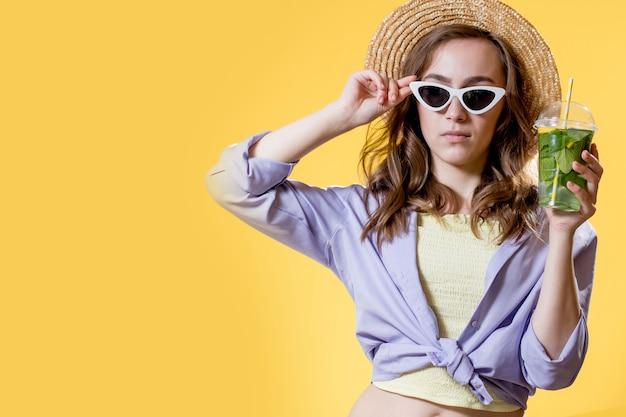 Ragazza in abito estivo che indossa occhiali da sole bianchi alla moda e si diverte bevendo un cocktail mojito. in posa sullo sfondo giallo.