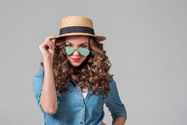 La ragazza in occhiali da sole e cappello di paglia sul muro grigio