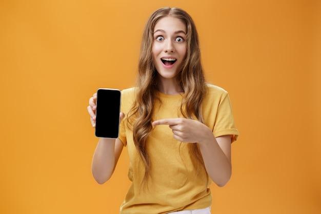 Ragazza sorpresa dalle fantastiche funzioni dello smartphone. ritratto di donna snella europea sveglia felice e stupita con acconciatura naturale ondulata che mostra il cellulare che punta allo schermo del gadget all'app. copia spazio