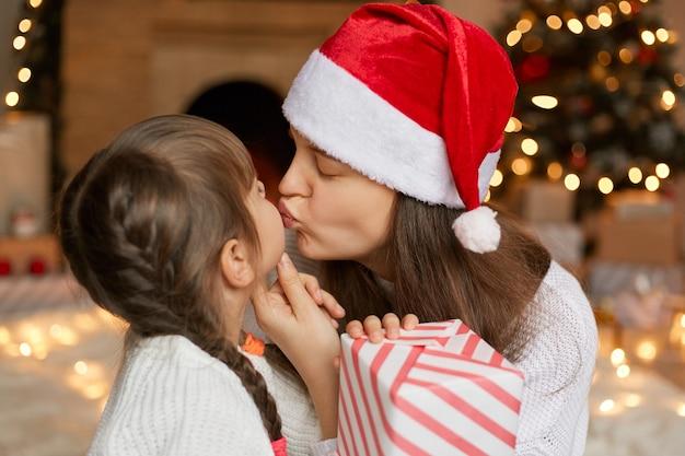 Ragazza che sorprende sua madre con un regalo di natale, mamma che bacia il suo bambino con gli occhi chiusi,