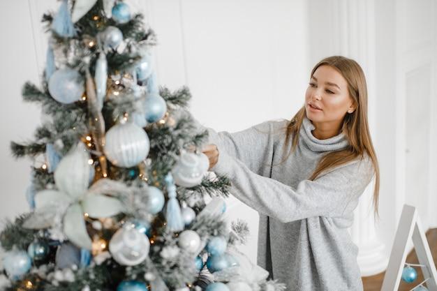 Una ragazza con un maglione decora un albero di natale. anno nuovo concetto.