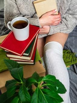 Una ragazza con un maglione beve il tè e legge i libri con piacere. la ragazza analizza la biblioteca di casa con vecchi libri.