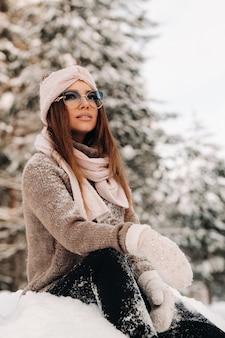 Una ragazza con un maglione e occhiali in inverno siede su uno sfondo coperto di neve nella foresta