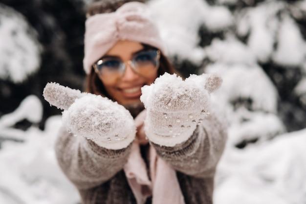 Una ragazza in maglione e occhiali in inverno in una foresta innevata