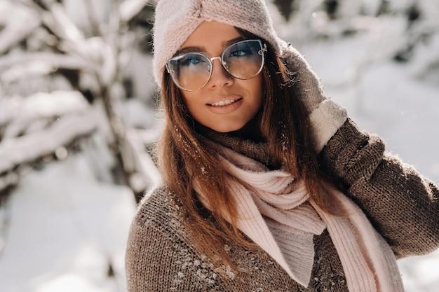 Una ragazza con un maglione e occhiali in inverno in una foresta innevata