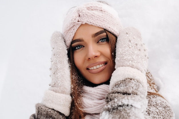 Una ragazza in maglione e guanti in inverno si trova su uno sfondo coperto di neve.