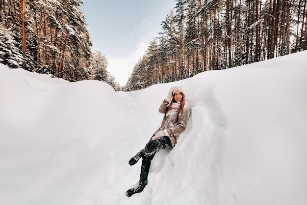 Una ragazza con un maglione e guanti in inverno si trova su una coperta di neve