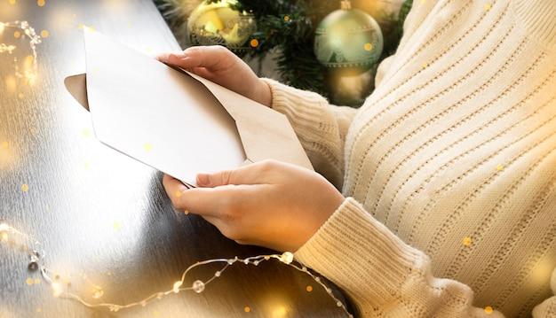 Una ragazza con un maglione si siede accanto a un albero di natale e legge una lettera