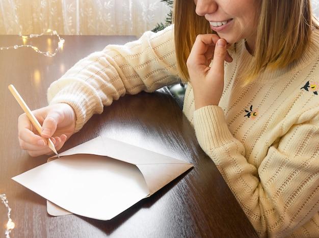 Una ragazza con un maglione si siede accanto a un albero di natale e scrive una lettera