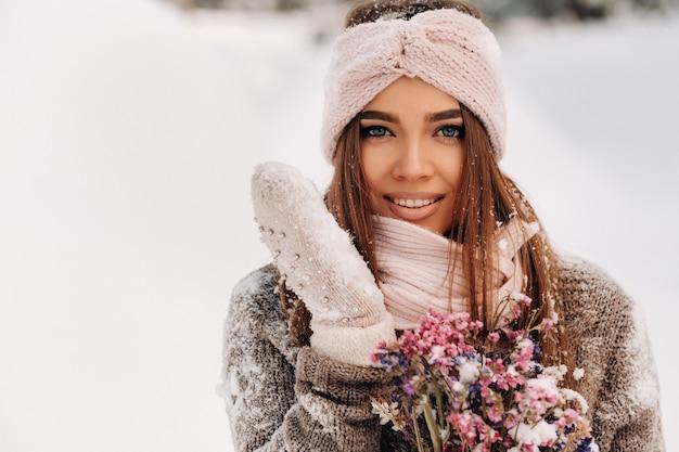 Una ragazza in un maglione in inverno con un bouquet tra le mani si trova tra grandi cumuli di neve.