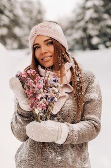 Una ragazza in un maglione in inverno con un bouquet in mano si trova tra grandi cumuli di neve.