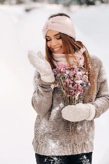 Una ragazza in un maglione in inverno con un bouquet in mano si trova tra grandi cumuli di neve