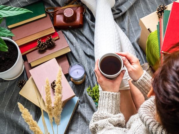 Una ragazza con un maglione senza volto è seduta su una coperta con i libri