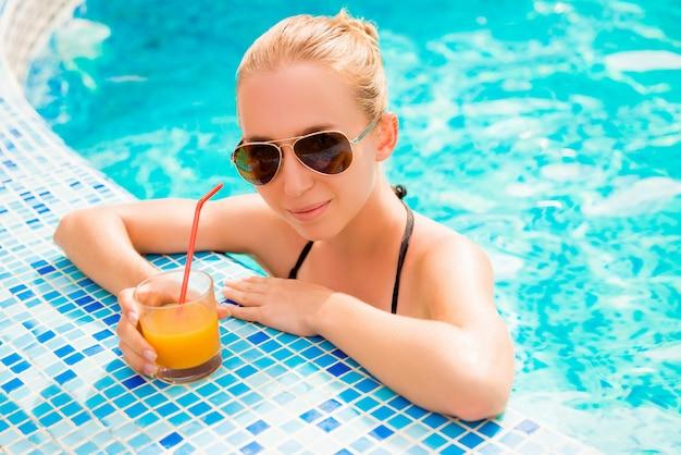 Ragazza che nuota in una piscina con succo e bicchieri