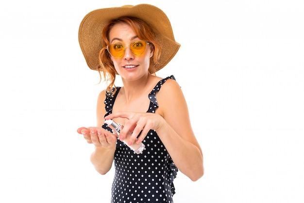 La ragazza in un costume da bagno sta applicando la crema solare su una parete bianca