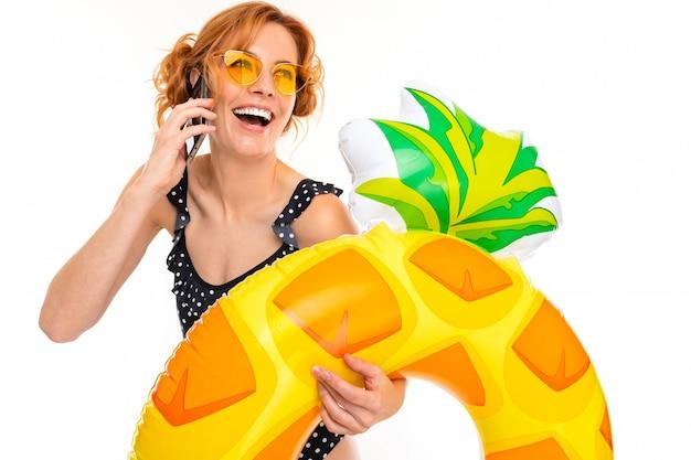 Ragazza in costume da bagno parlando al telefono mentre si tiene un cerchio di nuoto su un muro bianco