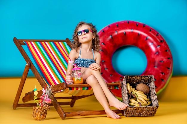 Ragazza in costume da bagno e occhiali da sole che si siede nella sedia a sdraio arcobaleno