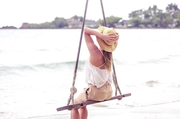 Ragazza su un'altalena sulla spiaggia della thailandia
