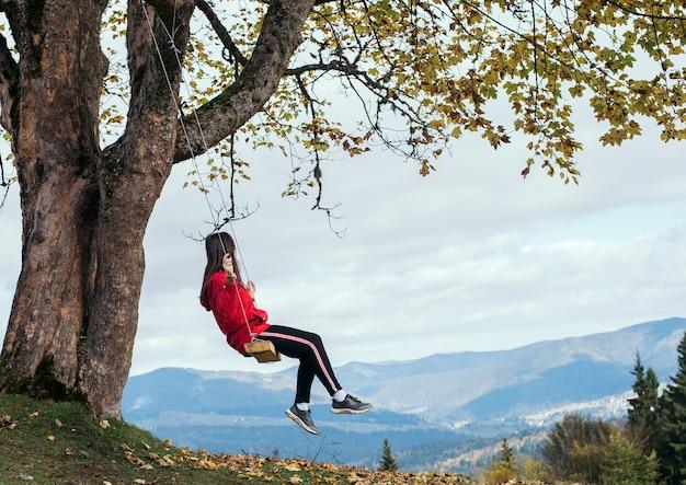 Ragazza su un'altalena in vacanza con vista sulle montagne e sulle foreste.
