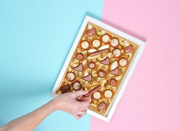 La ragazza prende una caramella al cioccolato da una scatola di cioccolatini con un vassoio d'oro su sfondo blu pastello rosa.
