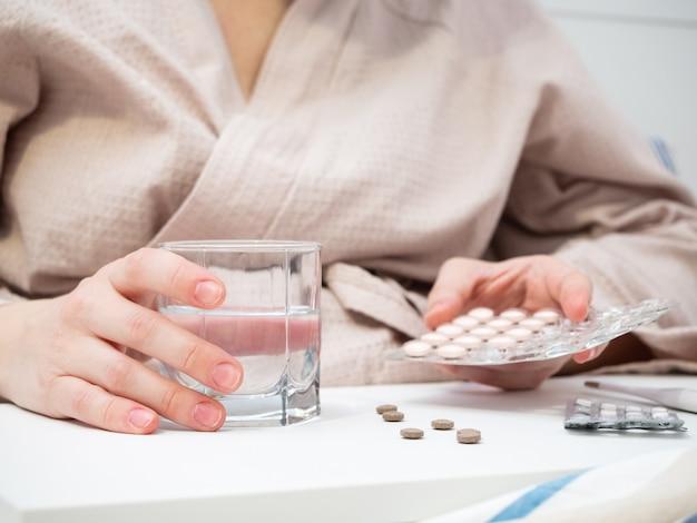La ragazza prende molte pillole diverse nel bel mezzo di un'epidemia di coronavirus e influenza.