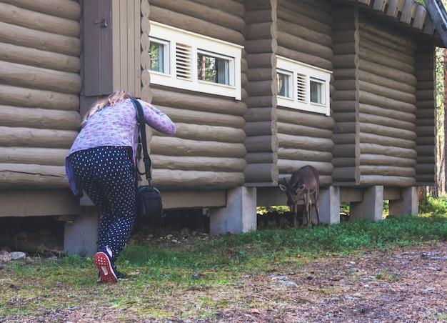 Una ragazza fa una foto a un cervo vicino a una casa di tronchi