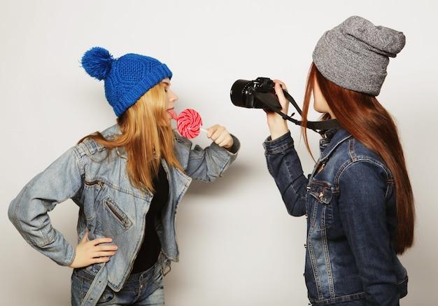 Una ragazza scatta una foto della sua amica di fronte su sfondo bianco